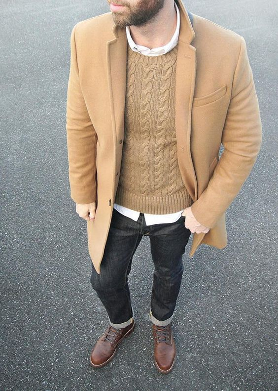camel topcoat over a cable-knit sweater and a white button down shirt with black denim