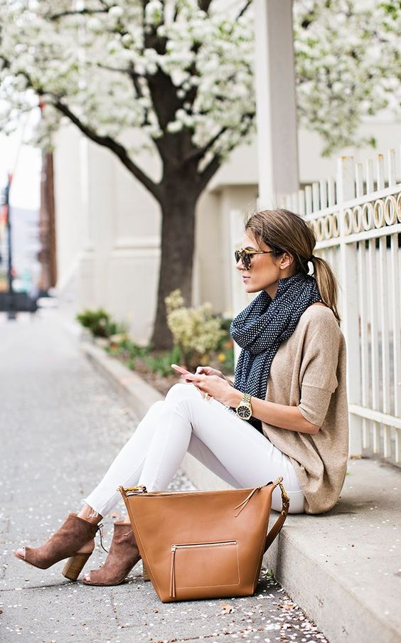 white jeans, a neutral sweater, cutout booties and a scarf