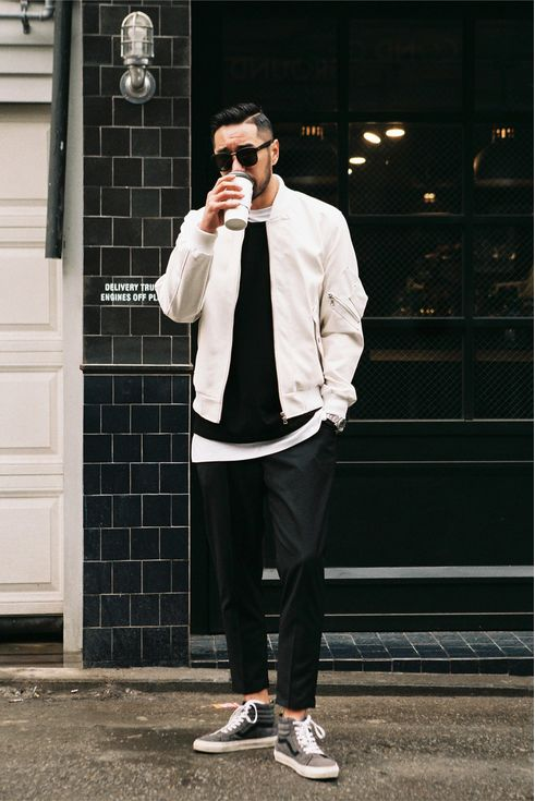 layered look with black pants, a white bomber jacket,a black sweater and grey chucks