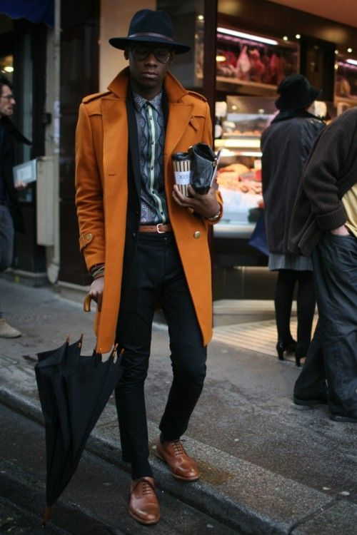 ocher coat, black pants, a printed shirt and brown boots