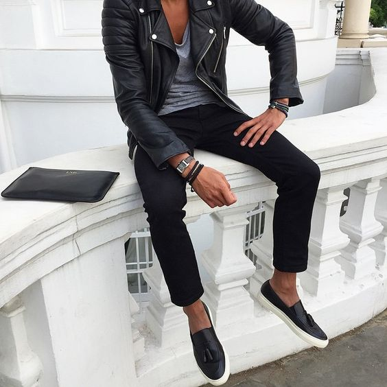 black trousers, a grey t-shirt, a black leather jacket and slip-ons
