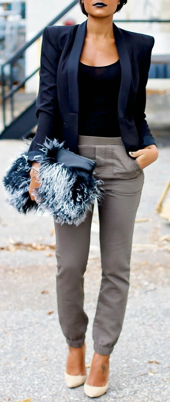 grey trousers, a black top, a navy shoulderpad jacket and a fluffy clutch