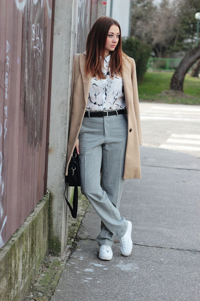 grey pants, a printed shirt, white sneakers and a camel coat
