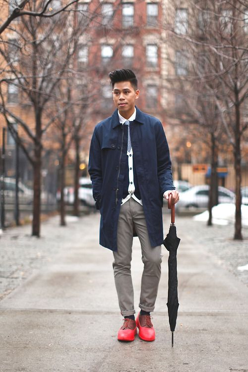 grey pants, a navy rain coat and red boots
