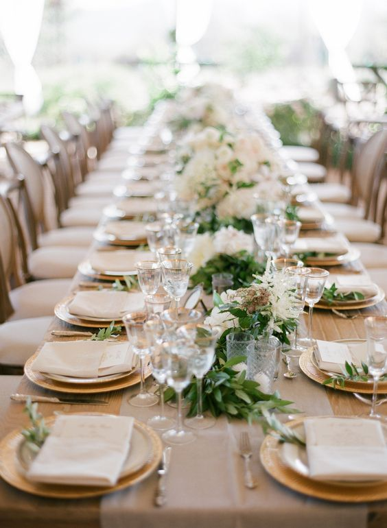garland running the length of the table, gold-rimmed stemware, gold chargers