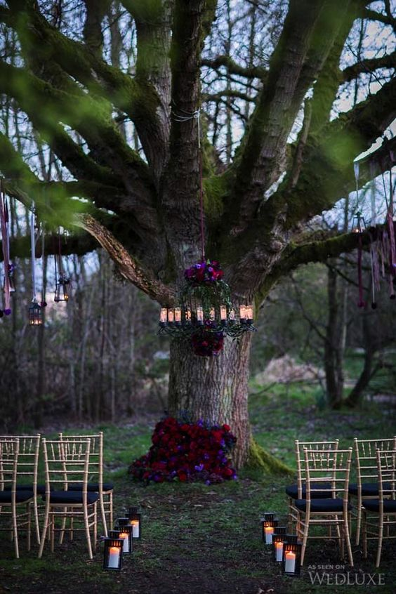 moody florals on the tree and chandelier make the ceremony spot chic
