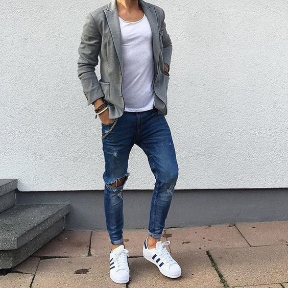 ripped blue jeans, white chucks, a white tee and a grey jacket