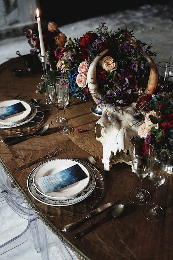moody table setting with a skull and flower centerpiece