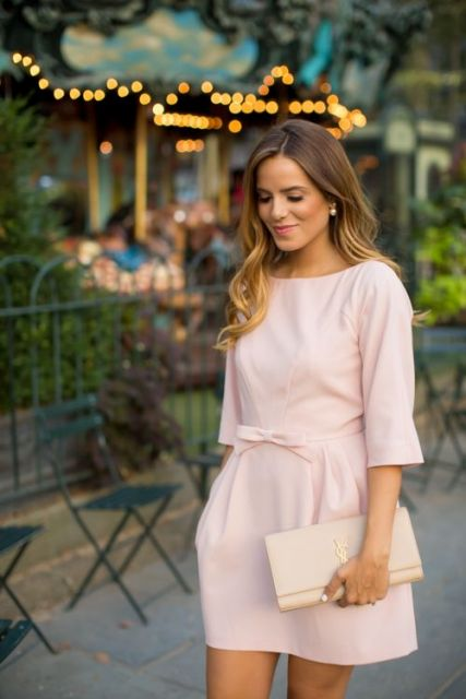 Mini dress with bow belt and cream clutch