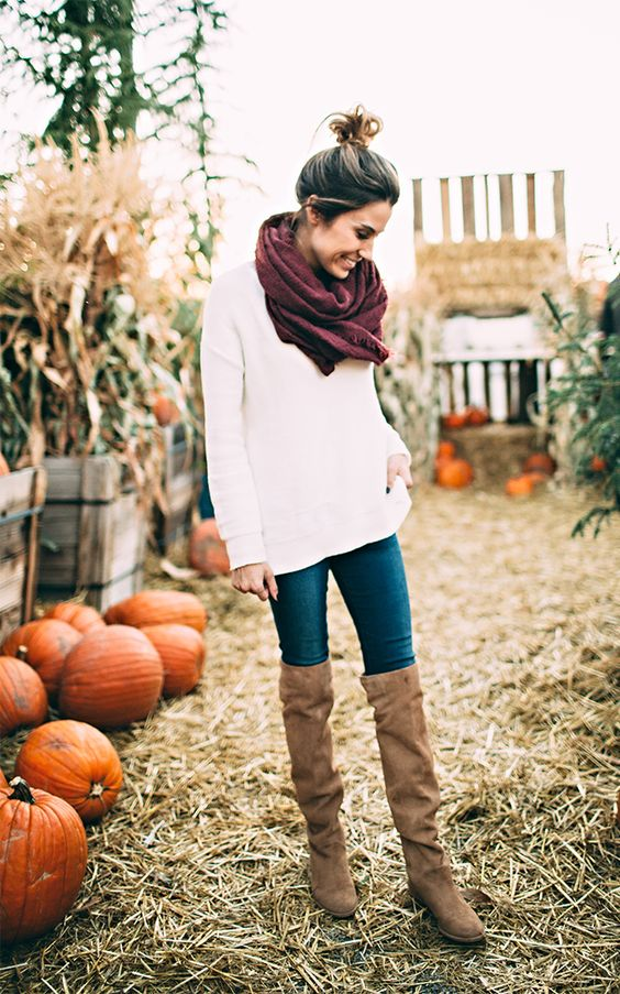 white sweater, blue jeans, a burgundy scarf and brown high boots