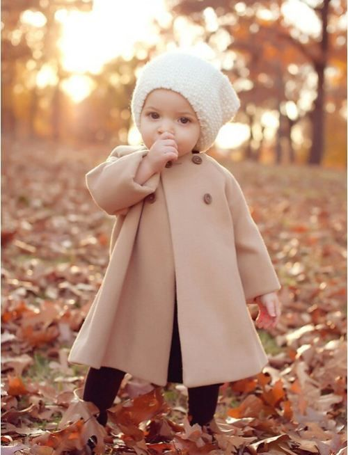 nude coat, black leggings and a white knit hat