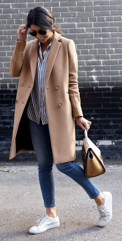 blue cropped jeans, a striped shirt, white sneakers and a camel coat