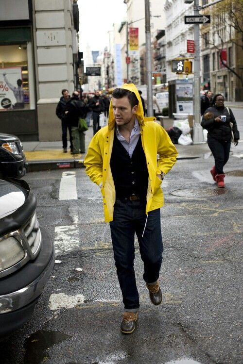 navy jeans, a black cardigan and a yellow rain coat