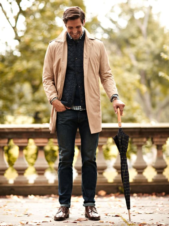 jeans, a quilted vest, a peach trenchcoat and brown shoes