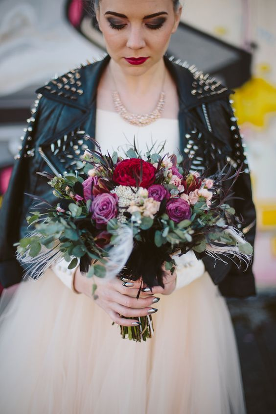 grunge bride in an ivory dress, a spiked leather jacket with bold makeup
