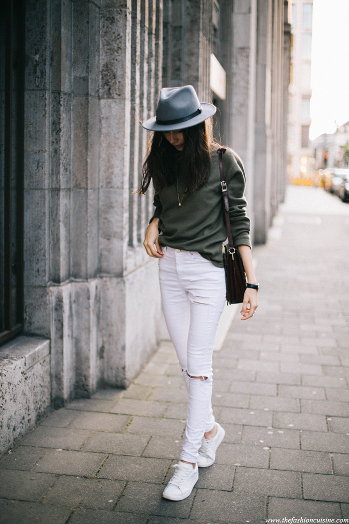 white ripped jeans, an olive green sweater and white sneakers