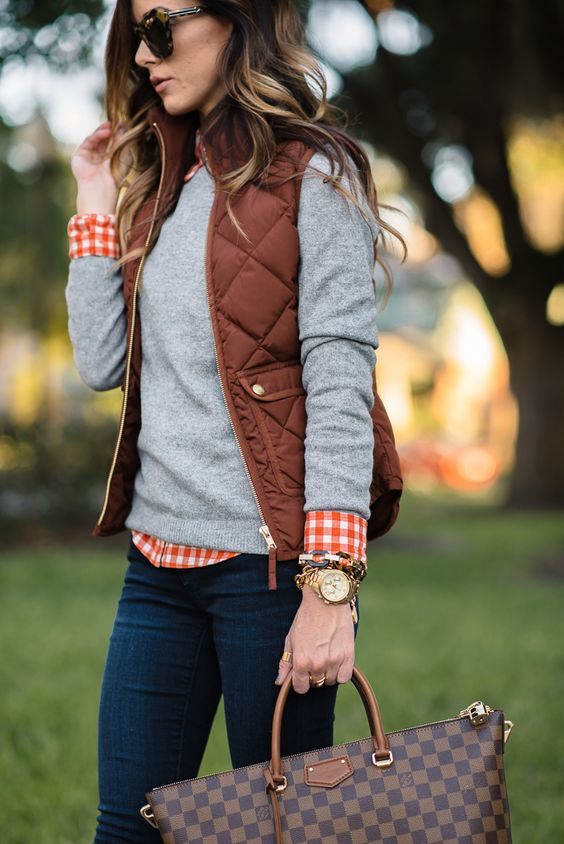 a grey jersey, a plaid shirt, a puffed vest and jeans