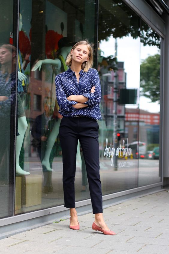 navy trousers, a dotted blue shirt and pink flats