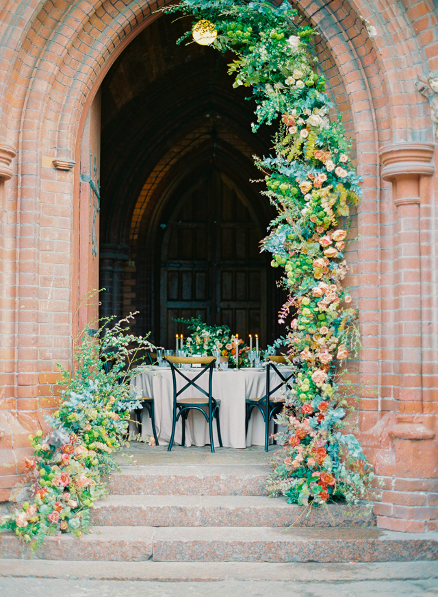 Peach and green flower adorned church entrance | Kir & Ira Photography