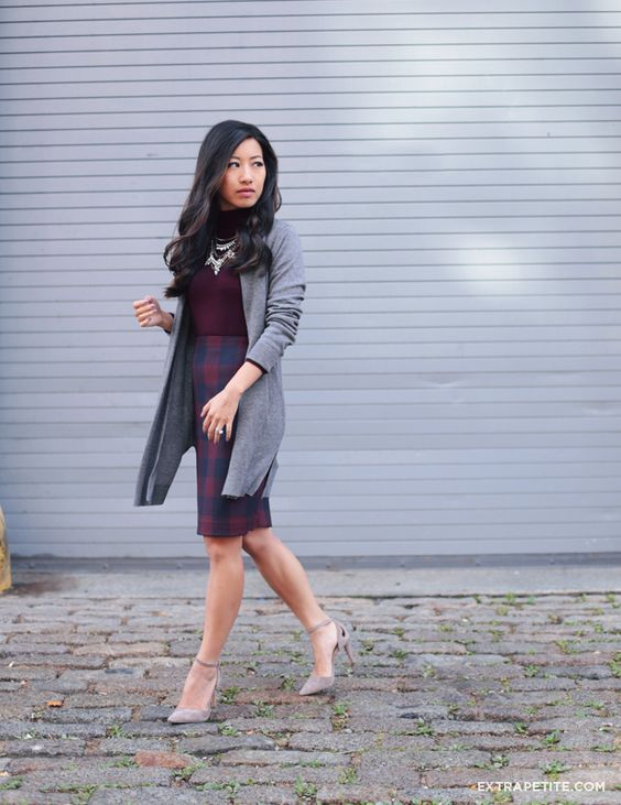 plaid skirt, a burgundy turtleneck, a statement necklace, a long grey cardigan and heels