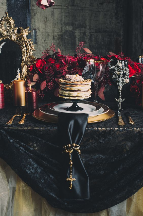 deep red florals, black lace tablecloth and a black napkin are perfect for a gothic wedding.