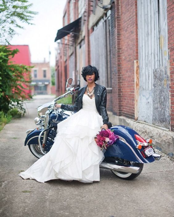 ruffled wedding dress with a black zip leather jacket and a statement necklace