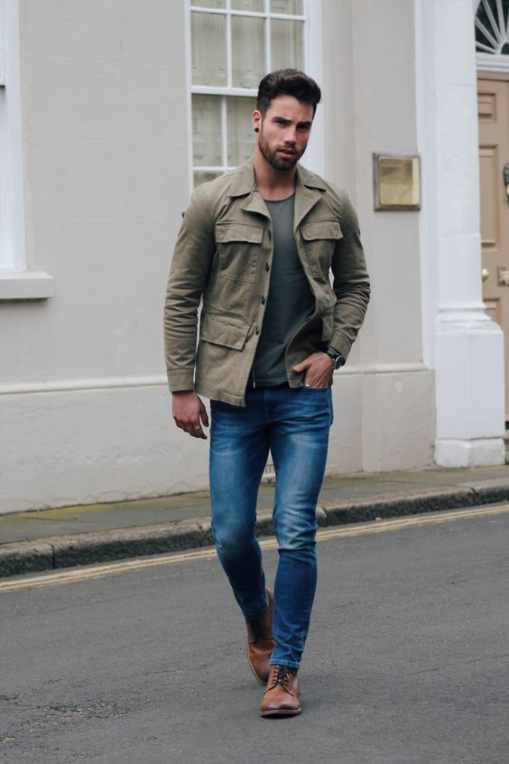 blue jeans, a dark grey t-shirt and an olive grey military jacket