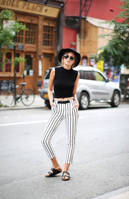 With black top, black hat and flat sandals