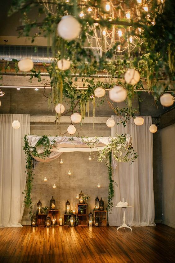 wedding chuppah with greenery, hanging candle holders and candle lanterns for indoors