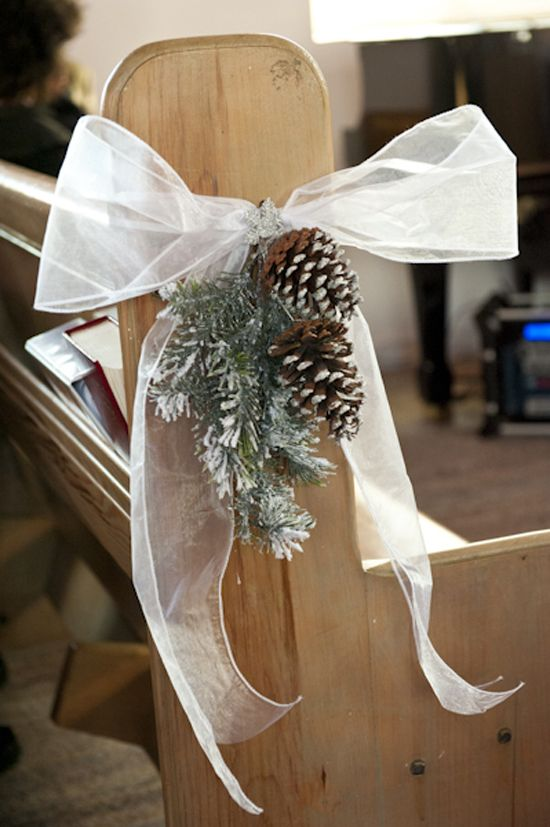 pinecone and snowy fir branches with a bow for aisle decor