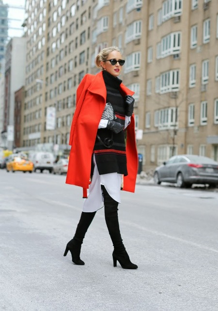 With white dress, oversized black sweater, over the knee boots and printed clutch