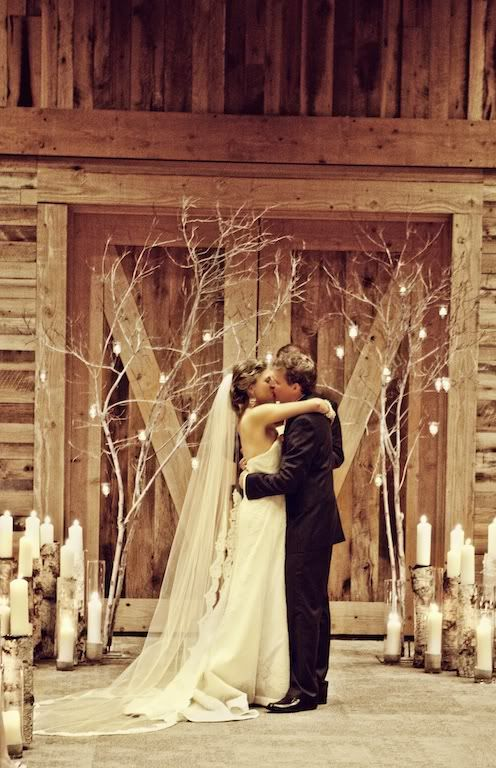 branches decorated with candles and birch log cnadle holders for a rustic big day