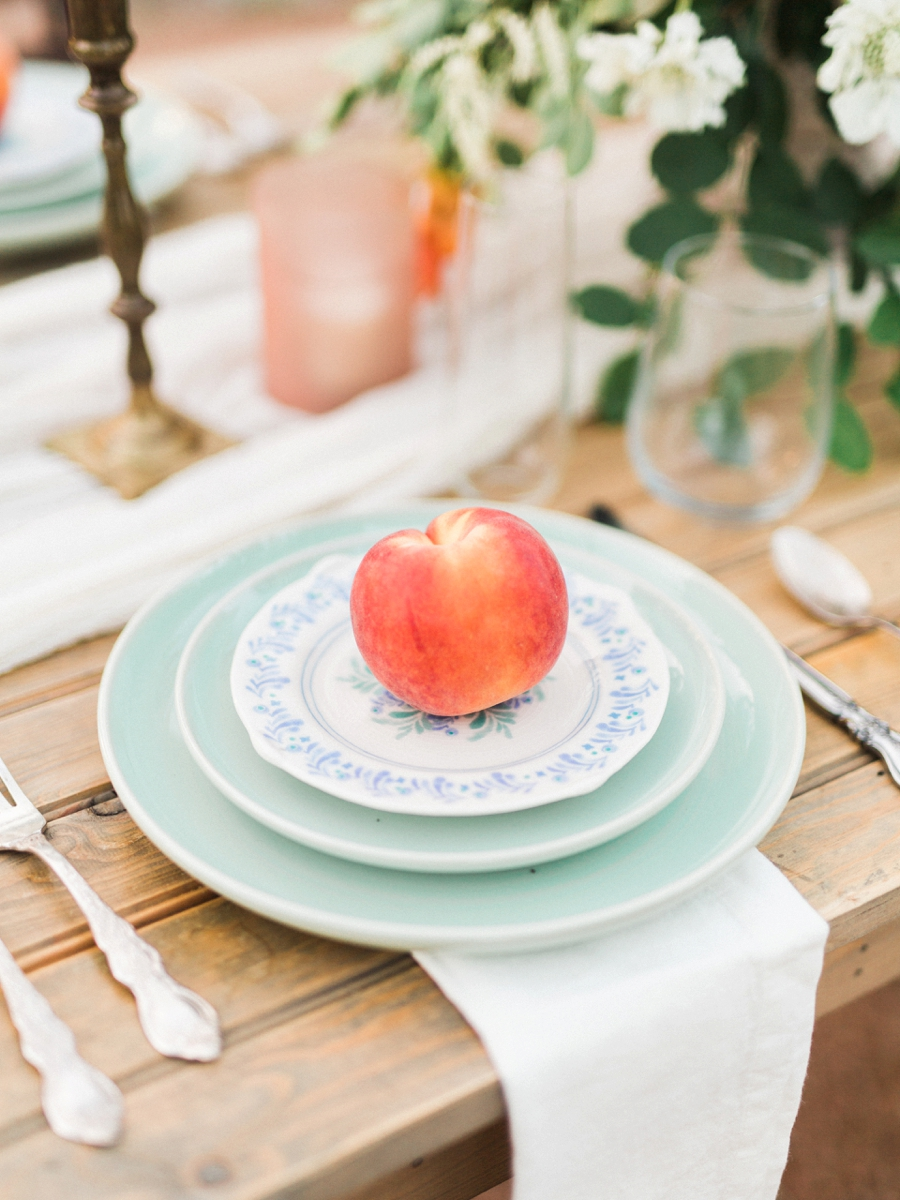 place setting with a peach - http://ruffledblog.com/watercolor-greenhouse-wedding-inspiration