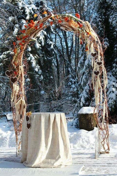 frosted outdoor winter arch with orange flowers and fabric hearts hanging