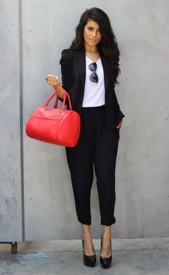 black pant suit, a white top, heels and a red bag