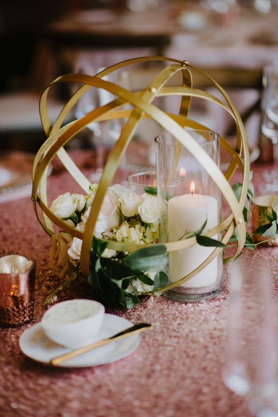 geometric gold sphere centerpiece with flowers and candles