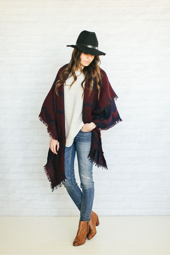jeans, a white sweater, brown boots and a burgundy and black scarf