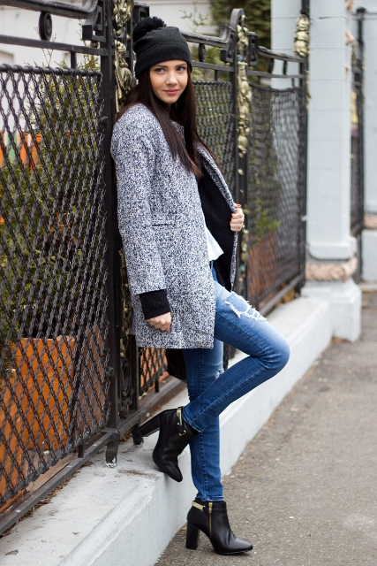 With distressed jeans, black ankle boots and hat