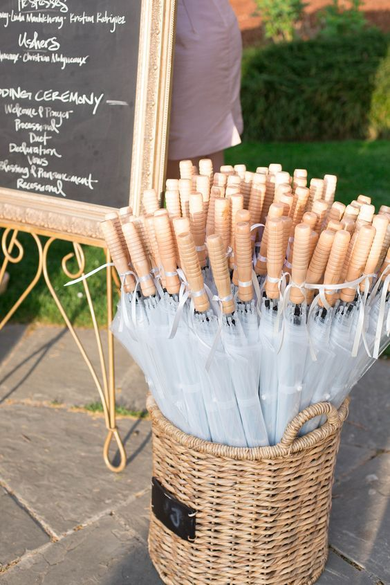 basket of clear umbrellas for wedding guests