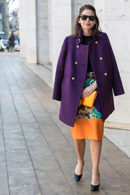 With black shirt, colorful printed knee-length skirt and clutch