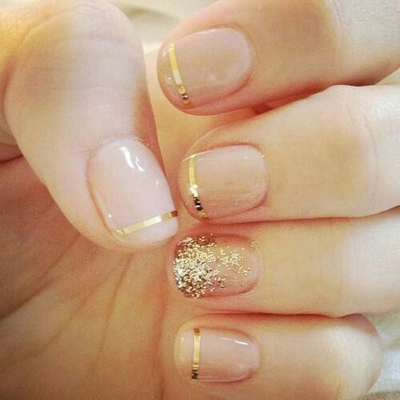French mani with gold striped and a glitter accent nail