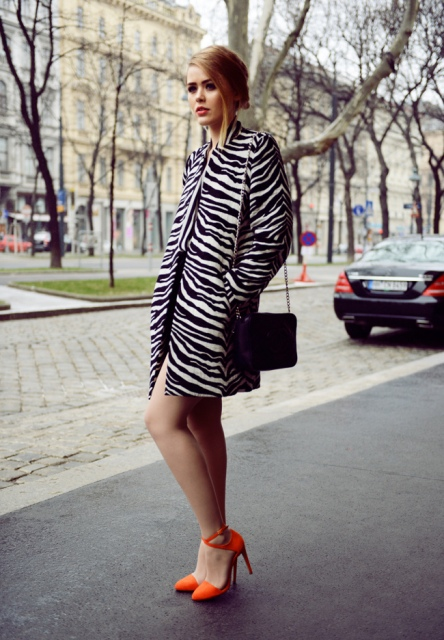 Zebra print coat with orange heels and black mini bag