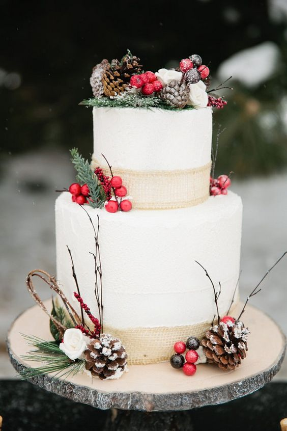 cake decorated with burlap, pinecones, berries and branches