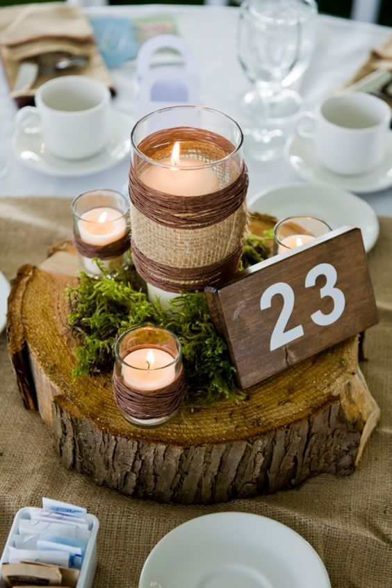 wood slice centerpiece with moss and candles and table numbers on a wood piece
