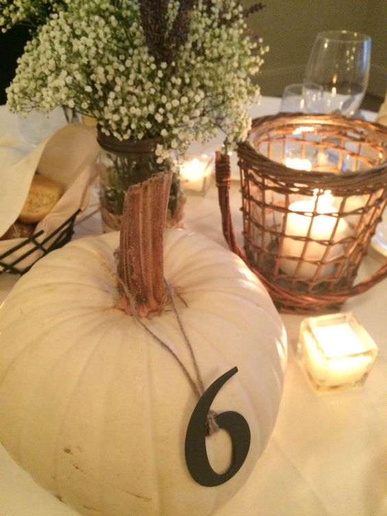 table number hanging on a white pumpkin for fall nuptials