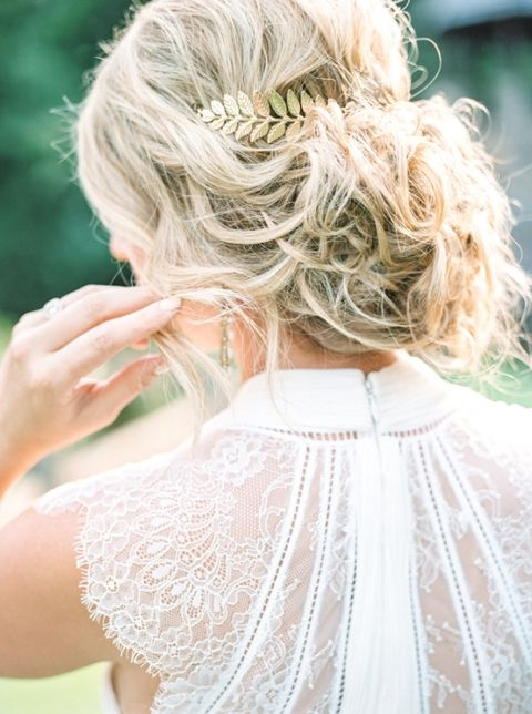 messy blonde wavy updo with a gold hairpiece