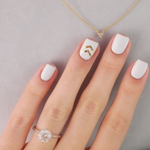 white nails with gold chevron stickers