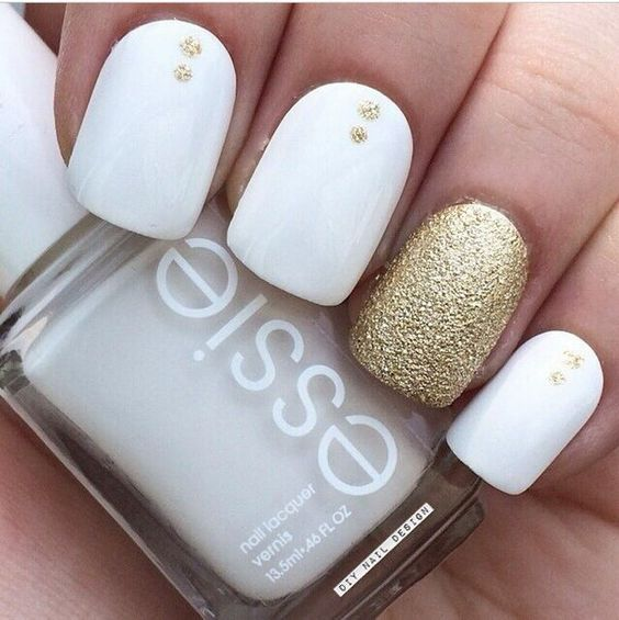 white nails with gold glitter dots and a gold accent nail