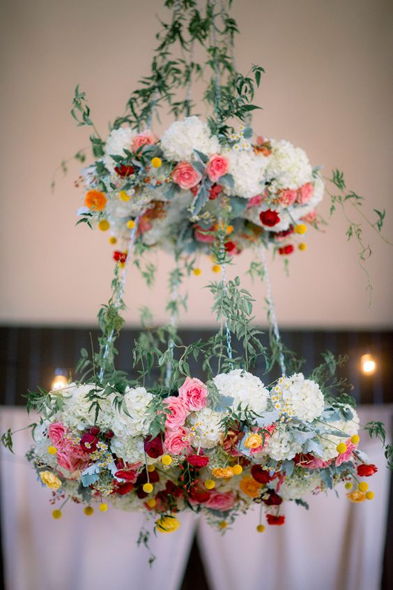 two tier floral chandelier with bold colors and greenery can fir a boho wedding