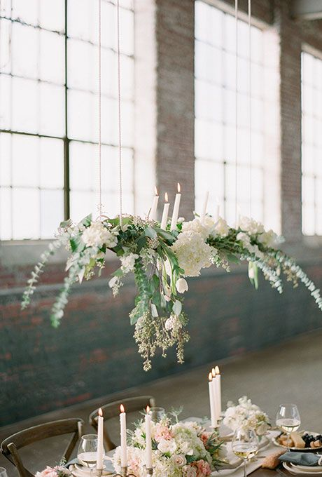 ferns and assorted white flowers suspended above tables in this warehouse venue add a touch of romance